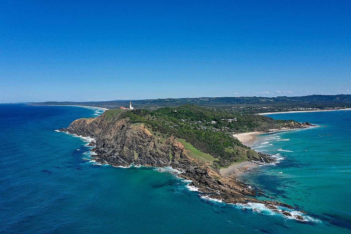 Фарът, плажът и вътрешността на залива Байрън Бей - въздушна снимка в Северните реки, Нов Южен Уелс, Австралия