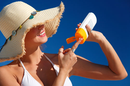 woman with hat applying sunscreen 6665